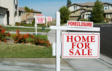 Row of Foreclosure Home For Sale Real Estate Signs in Front of Houses.